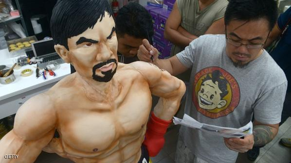 Zach Yonzon (R), creative director and owner of Bunny Baker Cafe, decorates a life-size 70 pound (31.75 kilogram) cake worth 4,000 USD in the image of Philippine boxer Manny Pacquiao at the bake shop in Manila on May 2, 2015. The cake, which took a week to bake and assemble, was made to commemorate the upcoming fight between Pacquiao, considered a national icon, and his rival American Floyd Mayweather. Yonzon said if Pacquiao wins, he will serve the cake for free to his customers.   AFP PHOTO / Jay DIRECTO        (Photo credit should read JAY DIRECTO/AFP/Getty Images)