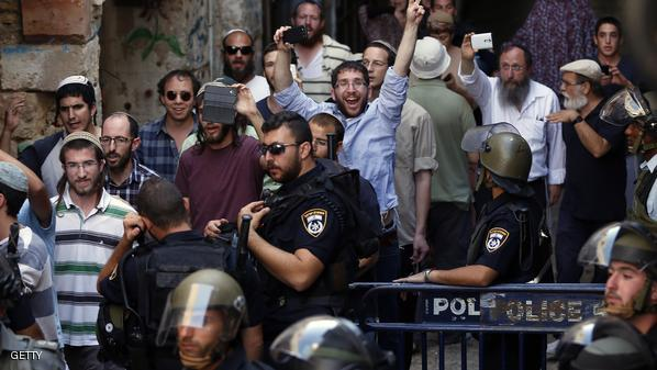 Israeli security forces stand guard as a group of Jewish young men, one flashing the sign of victory, leave after visiting al-Aqsa mosque compound during clashes between Palestinian protesters and Israeli police after authorities limited access for Muslim worshipers to the flashpoint al-Aqsa on July 26, 2015 in the old city of Jerusalem. Israeli police entered the compound, one of Islam's holiest places, to tackle suspected Palestinian rioters, police said. AFP PHOTO / AHMAD GHARABLI        (Photo credit should read AHMAD GHARABLI/AFP/Getty Images)