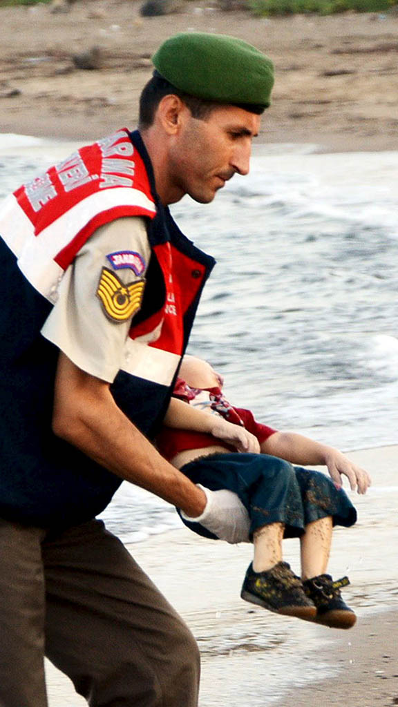 REFILE - CORRECTING BYLINEATTENTION EDITORS - VISUALS COVERAGE OF SCENES OF DEATH OR INJURYA Turkish gendarmerie carries a young migrant, who drowned in a failed attempt to sail to the Greek island of Kos, in the coastal town of Bodrum, Turkey, September 2, 2015. At least 11 migrants believed to be Syrians drowned as two boats sank after leaving southwest Turkey for the Greek island of Kos, Turkey's Dogan news agency reported on Wednesday. It said a boat carrying 16 Syrian migrants had sunk after leaving the Akyarlar area of the Bodrum peninsula, and seven people had died. Four people were rescued and the coastguard was continuing its search for five people still missing. Separately, a boat carrying six Syrians sank after leaving Akyarlar on the same route. Three children and one woman drowned and two people survived after reaching the shore in life jackets. REUTERS/Nilufer Demir/DHA  TPX IMAGES OF THE DAY     ATTENTION EDITORS - NO SALES. NO ARCHIVES. FOR EDITORIAL USE ONLY. NOT FOR SALE FOR MARKETING OR ADVERTISING CAMPAIGNS. THIS IMAGE HAS BEEN SUPPLIED BY A THIRD PARTY. IT IS DISTRIBUTED, EXACTLY AS RECEIVED BY REUTERS, AS A SERVICE TO CLIENTS. TURKEY OUT. NO COMMERCIAL OR EDITORIAL SALES IN TURKEY. TEMPLATE OUT