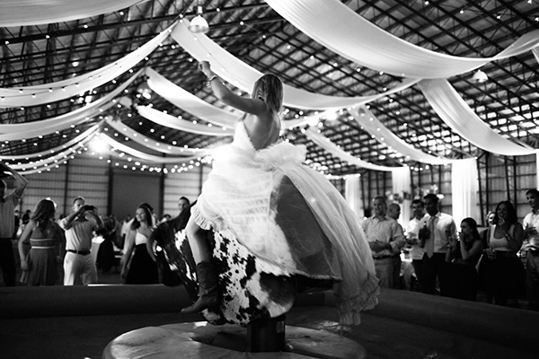 bride rides mechanical bull at wedding reception by gia canali