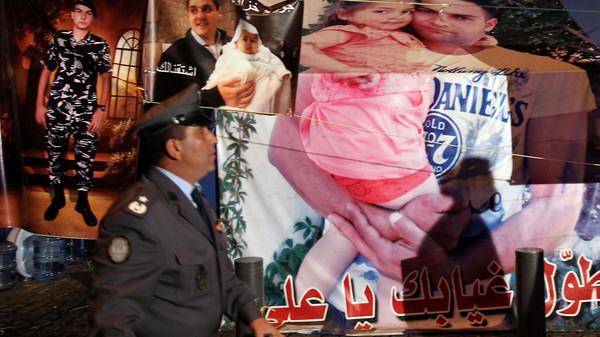 A Lebanese policeman walks past posters showing one of the Lebanese soldiers, who was kidnapped by Islamic militants, carrying his daughter, on a tent occupied by his family outside the government palace in downtown Beirut as they hold a sit-in late on December 5, 2014. The Al-Qaeda-linked Syrian extremist group the Al-Nusra front claimed to have killed a captured Lebanese soldier to avenge the arrest of the daughter and former wife of Abu Bakr al-Baghdadi, who leads the Islamic State jihadist group. AFP PHOTO/ANWAR AMRO
