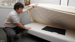 TO GO WITH AFP STORY BY REBECCA FRASQUET An engineer of the CSTB (Centre scientifique et Technique du Batiment), a research, testing, certification and training organisation working primarily in the built environment and construction, shows a smart object placed under a mattress and dedicated to Ambient Assisted Living programs, on June 18, 2015 at the French technopole of Sophia Antipolis in Valbonne, southeastern France. AFP PHOTO / JEAN-CHRISTOPHE MAGNENET (Photo credit should read JEAN-CHRISTOPHE MAGNENET/AFP/Getty Images)