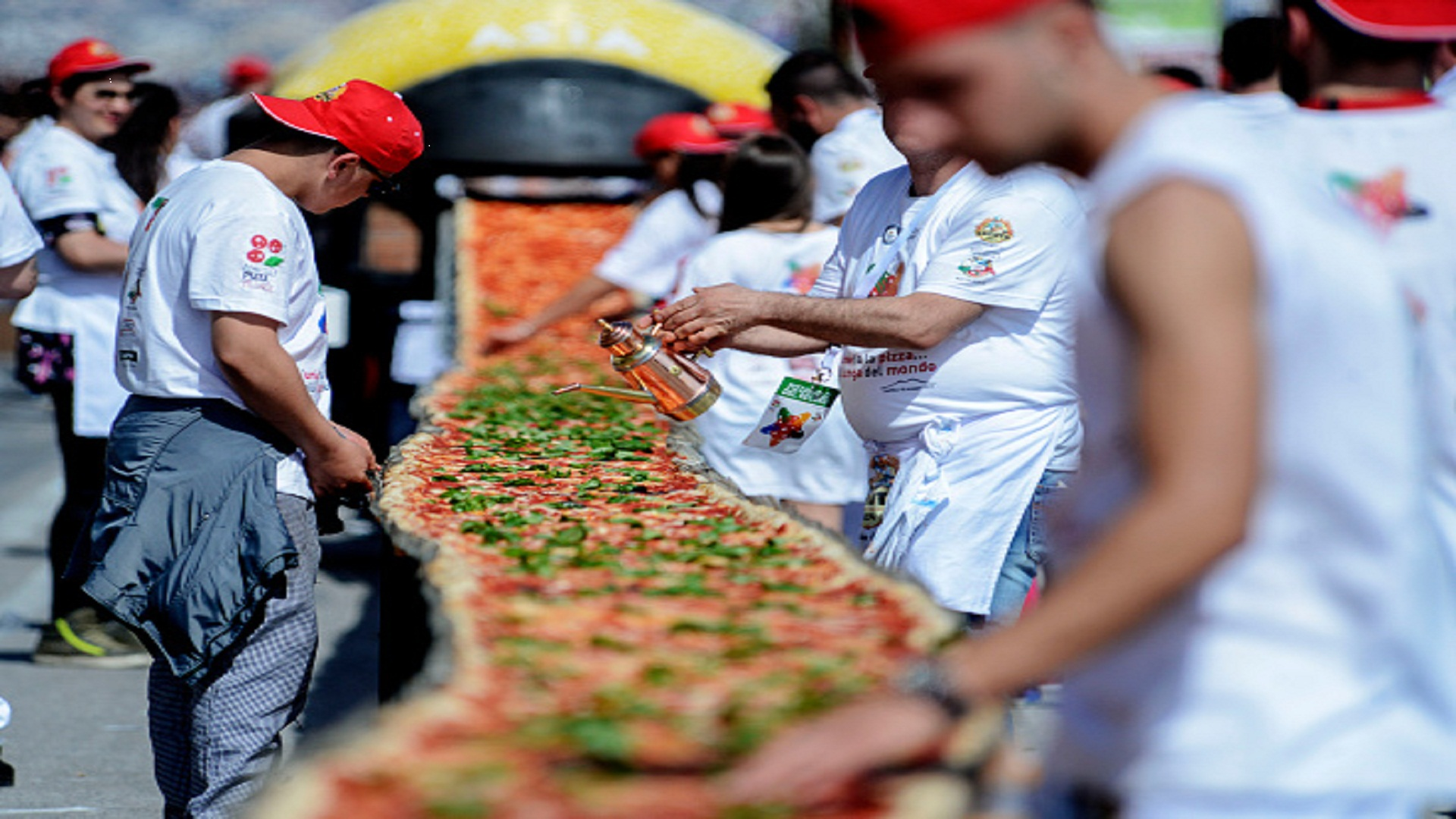 Neapolitan pizza makers attempt to make the longest pizza to break a Guinness World Record along the seafront of Naples, on May 18, 2016. For the wood-fired pizza, which measured two kilometres, they used 2,000 kg of flour, 1,600 kg of tomatoes, 2,000 kg of mozzarella, 200 litres of oil, 30kg of fresh basil. / AFP / Mario LAPORTA (Photo credit should read MARIO LAPORTA/AFP/Getty Images)