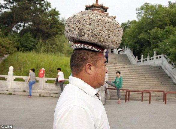 صيني يحمل حجراً على رأسه ليخسر الوزن الزائد