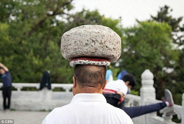 صيني يحمل حجراً على رأسه ليخسر الوزن الزائد1