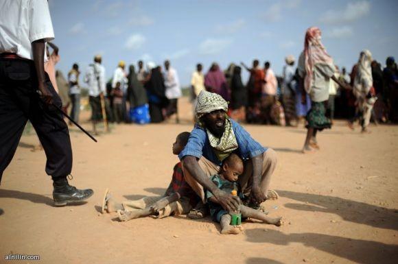 رجل صومالي يحمي طفليه في معسكر للاجئين الصوماليين في شمال كينيا اثناء توزيع الطعام 5-7-2011