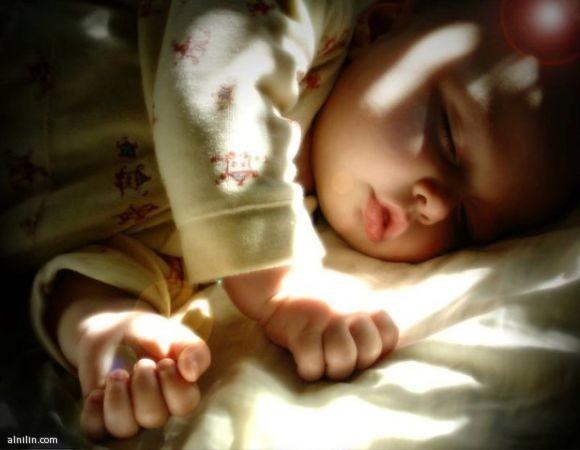طفل مستغرق في النوم و قد اطلت عليه اشعة الشمس