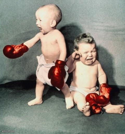 طفلان يتلاكمان و الفائز يحتفل بالنصر بالتعبير عن فرحته و المهزوم يبكي