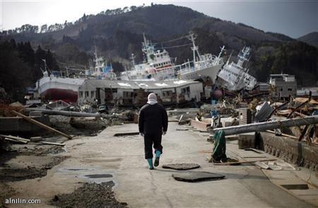 رجل يسير بجوار ميناء دمره الزلزال وموجات المد العاتية في اليابان 28-3-2011